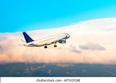 Airplane flying in the sky above Sofia Bulgaria with clouds and mountains at the background