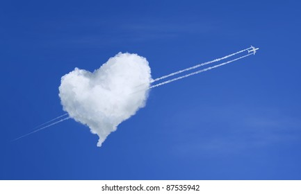 Airplane flying through heart shaped cloud