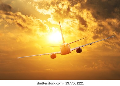 Airplane flying towards the sun silhouette at sunset