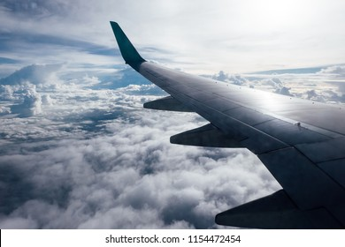 Airplane flying and traveling, view from airplane window on the wing with blue sky and cloud.