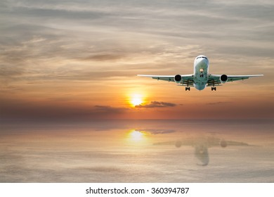 Airplane flying tropical sea at sunset time with reflection.