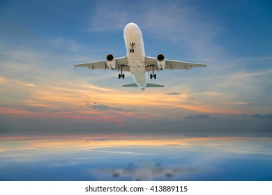 Airplane flying tropical sea at sunset time
