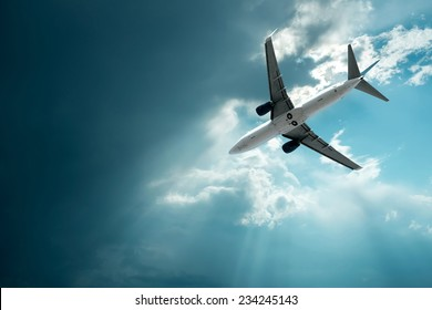 Airplane at flying under sky with clouds