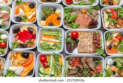 Airplane food presentation with variety of in flight meals.  Flight catering.  Food on airplanes. Salad bar buffet  display in restaurant.  Meat cuts. Hot appetizers. Close-up, a lot of food.
