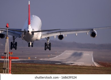 Airplane with four engines landing on runway back view - moments before touchdown