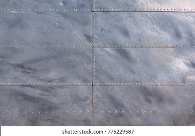 Airplane fuselage silver metal texture with rivets. Useful as background for design works.