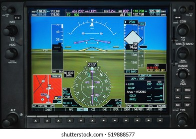 Airplane glass cockpit display with terrain and engine gauges in small private airplane