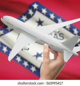 Airplane in hand with local US state flag on background series - Arkansas
