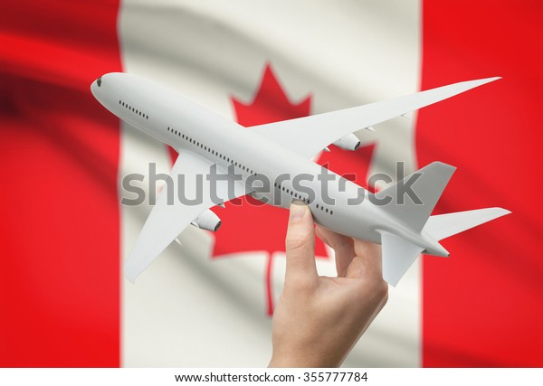 Airplane in hand with national flag on background - Canada