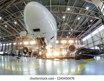 Airplane in the hangar for maintenance, bottom nose view