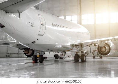 Airplane in hangar, rear view of aircraft and light from windows