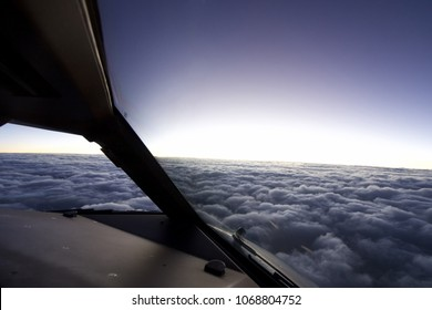 Airplane inside cockpit flying over cloudy sky