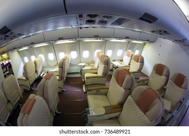 Airplane interior. The passenger cabin of modern long-range aircraft. Busines class. A rows of passenger seats.