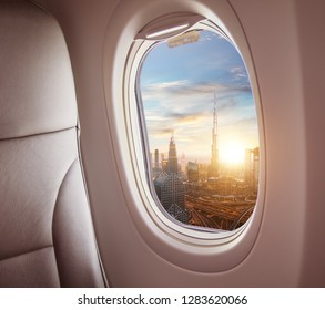 Airplane interior with window view of Dubai city, UAE. Concept of travel and air transportation