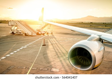Airplane at international airport ready for takeoff - Modern terminal gate at sunset - Travel trip concept around the world - Wide angle with warm vignetting filter and enhanced sunshine lens flare