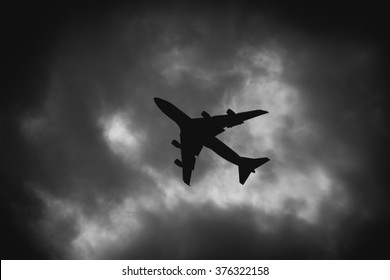 Airplane isolated in dark cloud background.