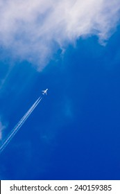 Airplane and jet trail on a blue sky heading into clouds