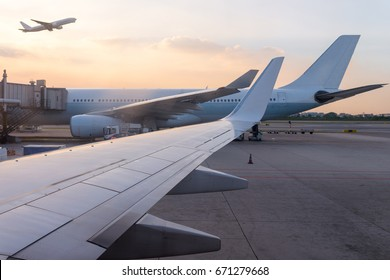 airplane jet waiting to runway on taxi lane in airport and aircraft traffic to take off with sunset background, view from window air plane