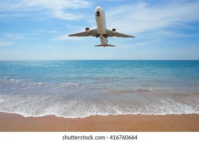 Airplane landing above beach