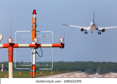 airplane landing with airport beacons in daylight