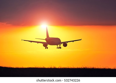 Airplane landing at the airport during amazing sunset.