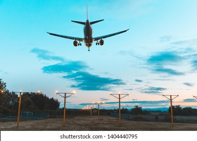 Airplane landing at the airport dusk - Silhouette of a commercial airliner approaching the runway after sunset - Teal and orange filter effect perfect for travel and wanderlust concepts