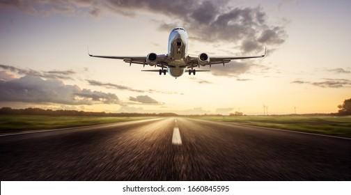 Airplane Landing  approaching runway at  sunrise