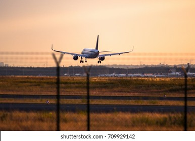 Airplane landing with clouds in the sky at sunset