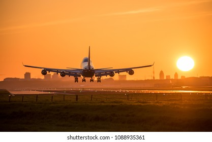 Airplane is landing during a bright sunrise at the airport.