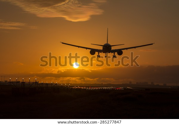Airplane is landing during a nice cloudy sunrise.