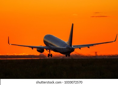 Airplane is landing during sunrise.