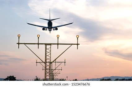 Airplane landing during sunset with copy space on the side. View of the approach lighting system ALS towers.