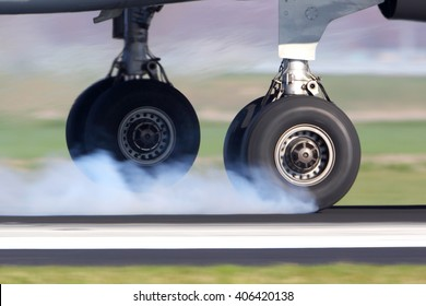 Airplane landing gear touching the runway with white smoke.