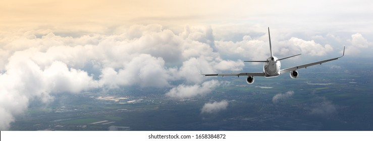 Airplane. Landscape with big white passenger airplane is flying iover the clouds  Journey. Passenger aircraft is landing at dusk. Business trip. Commercial plane