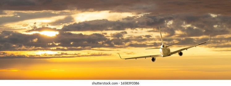 Airplane. Landscape with big white passenger airplane is flying in the yellow  sky  at colorful sunset. Journey. Passenger aircraft is landing at dusk. Business trip. Commercial plane