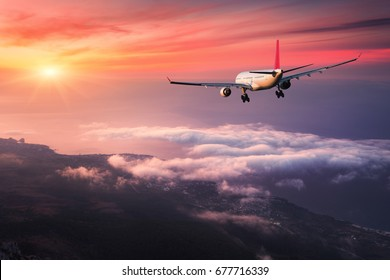 Airplane. Landscape with big white passenger airplane is flying in the red sky over the clouds at colorful sunset. Journey. Passenger aircraft is landing at dusk. Business trip. Commercial plane