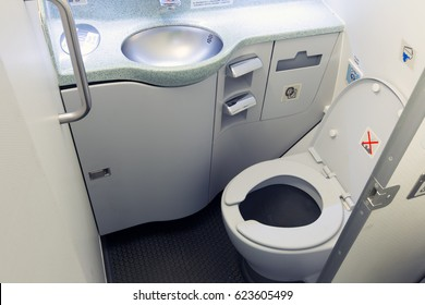 Airplane lavatory. Toilet seat and wash basin close-up.