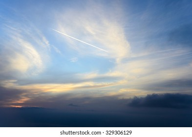 Airplane leaving a long trail on a beautiful cloudy sky