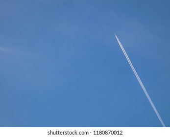 Airplane leaving white vapor trace in clear blue sky. Sunny day. Jet flying.