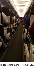Airplane line of seats filled with people in coach
