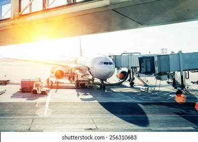 airplane loading in airport at sunset