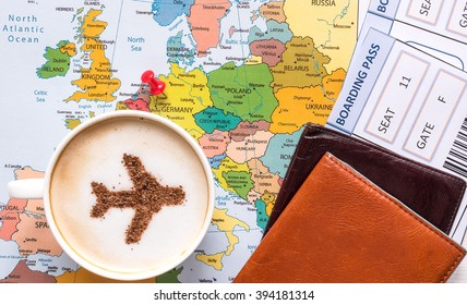 Airplane made of cinnamon in cappuccino, passports, Europe map and no name boarding pass.  Marked point of destination - Germany