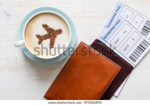 Airplane made of cinnamon in coffee.  Cup of coffee, passports and no name boarding passes. Traveling concept. Cappuccino in airport