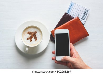 Airplane made of cinnamon in coffee,  white smartphone, passport and boarding pass