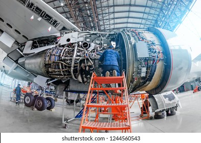 Airplane mechanic diagnose repairs jet engine through open hatch