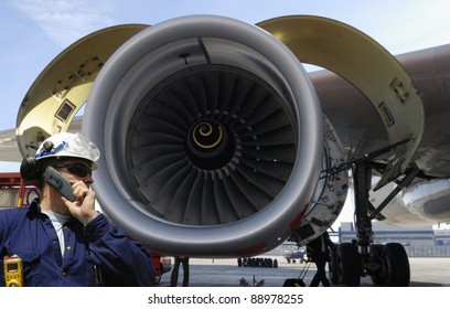 airplane mechanic with giant jet engine in background