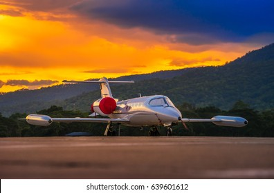 Airplane model of Bombardier Learjet 35A parking on the apron with beautiful sunset and mountain Background.