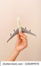 Airplane model in child's hand. Concepts of travel, education and journey dream on pink background.