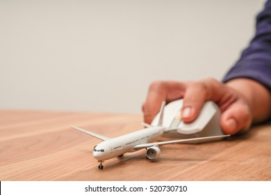 Airplane model and computer mouse on wooden desk, copy space on Left side, On line travel booking concept.