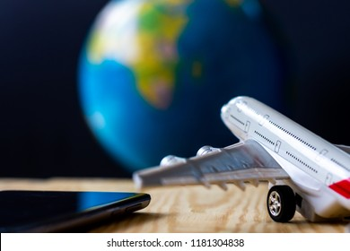 Airplane model, smartphone  on wooden floor with globe blur background. Technology and Air travel concept